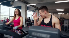 Athletic man and woman walking on treadmills, talking and smiling. Work out in a Arkistovideo