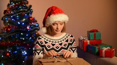 Woman in Santa hat unpacking Xmas gift Stock Footage