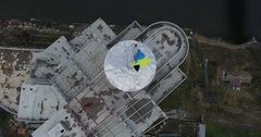 Aerial view of spire with Ukrainian flag on unfinished building Stock Footage