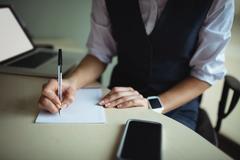 Businesswoman writing on notepad Stock Photos