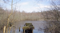 Decaying broken rotting boat dock, lake in forest, long shot, Germany Stock Footage
