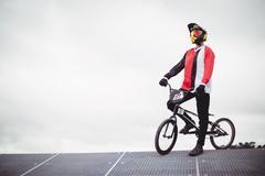 Cyclist standing with BMX bike on starting ramp Kuvituskuvat