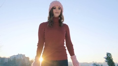 Winter of a young smiling woman in a pink hat and mittens on a background sunset Stock Footage