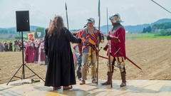 King is shaking hands of the two knights that are coming on stage Stock Footage