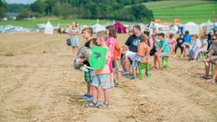 Children are standing in the middle of the field and are watching a performance Stock Footage