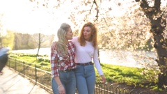 Two women walking at park in London Stock Footage