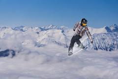 Snowboard rider jumping on mountains. Extreme snowboard freeride sport Stock Photos