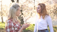 Two women talking at park in London Stock Footage