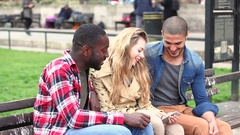 Multiracial group of friends looking at a smart phone Stock Footage