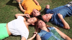 Friends lying and relaxing on the grass Stock Footage