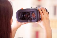 Young brunette woman holding up virtual reality goggles showing to camera, vr Stock Photos