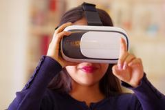 Young brunette woman wearing virtual reality goggles experiencing future Stock Photos