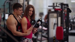 Sporty woman lifts dumbbells while working out in the gym. She is trying hard Stock Footage
