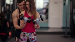 Sporty woman lifts dumbbells while training in a sport club. Athletic man is Stock Footage