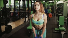 Strong woman doing exercise in gym. She lifting dumbbells. Stock Footage