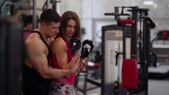 Sporty woman lifts dumbbells while working out in sport club. Athletic man is Stock Footage