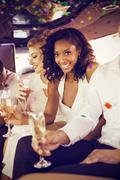 Composite image of well dressed woman drinking champagne in limousine Kuvituskuvat
