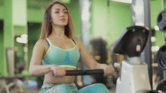 Woman make exercise on rowing machine in gym Stock Footage