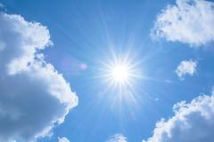Realistic shining sun with lens flare on blue sky clouds nature day  background Stock Photos