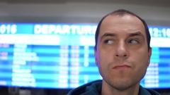 Worried caucasian man looking around near airport departure board. Tourism Stock Footage