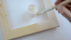Woman hand painting wooden picture frame on white color Stock Footage