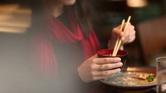 Young woman stirring noodle soba with sticks Stock Footage