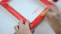 Woman hands erases the paint from the wooden picture frame using a sponge Stock Footage