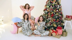 Three girls having fun in their pajamas near the Christmas tree Stock Footage