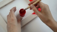 Woman hand painting wooden picture frame on red color Stock Footage