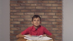 Child sitting at the desk holding flipchart with lettering freedom on the Stock Footage