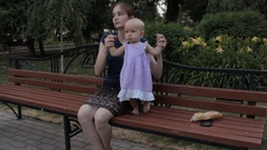 A girl holding a baby girl by both hands, the baby girls crouches as if dancing Stock Footage