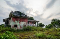Ruined mansion surrounded by lush green with dramatic sky Stock Photos