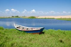 Fishing boat anchored in lagoon with green grass and dunes Stock Photos