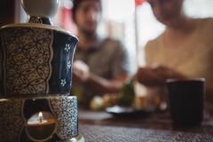 Close-up of lit candle in ceramic pot Stock Photos