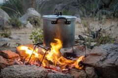 Aluminium pot being heated over outdoor camp fire Stock Photos