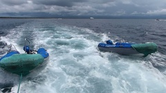Inflatable dinghies towed after yacht in Galapagos National Park, Ecuador Stock Footage