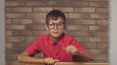 Child sitting at the desk holding flipchart with lettering discount on the Stock Footage