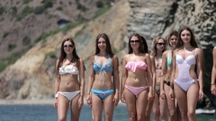 Attractive young women in bikinis running along the shore of the beach Stock Footage