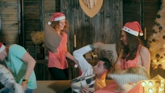 Fun pillow fight. Group of friends having fun, enjoying Christmas party together Stock Footage