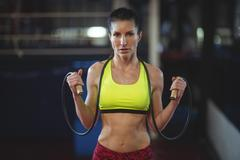 Sportswoman holding skipping rope in fitness studio Stock Photos