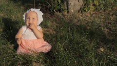 A girl sitting on the grass in a white and pink dress and a bonnet, opening her Stock Footage
