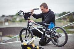 Cyclist repairing a BMX bike Kuvituskuvat