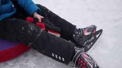 The happy child sits resting and smiling on the ice rink in skates Stock Footage