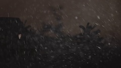Snow fall on gingerbread house surrounded by fir-trees and snow drifts Stock Footage