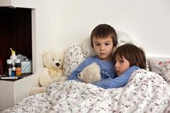 Two cute sick children, boys, staying in bed with fever Stock Photos
