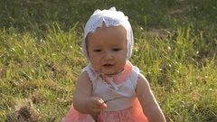 A toddler girl taking a stick in her hands and showing it into the camera Stock Footage