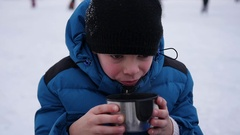 The kid is drinking hot tea from a mug in the winter outdoor. ice rink Stock Footage