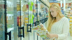 Attractive woman buying food at the supermarket. Read the newspaper with Stock Footage