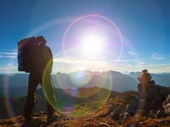 Lens flare defect.Man hiker with rucksack walk  on rocky peak. Man walking o Stock Photos