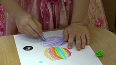 Child draws with colored pencils on paper. Stock Footage